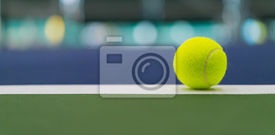 one new tennis ball on white line in blue and green hard court with beautiful bokeh, copy space on left