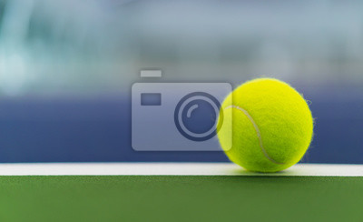 one new tennis ball on white line in blue and green hard court with copy space on left