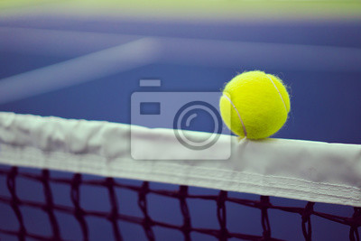 one new tennis ball on white stipe of net in blue and green hard court with copy space on left