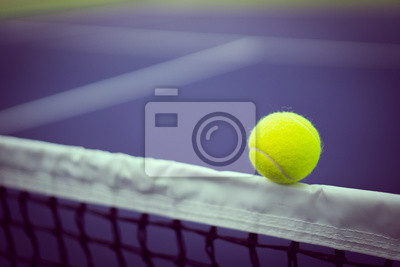one new tennis ball on white stipe of net in purple hard court with copy space on left