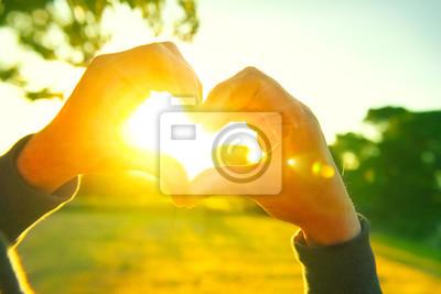 Naklejka Osoba dokonywania serce z rąk nad charakter tła słońca. Silhouette ręce w kształcie serca z słońcem wewnątrz