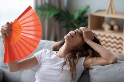 Naklejka Overheated woman sitting on couch, waving orange paper fan close up, girl feeling unwell, suffering from heating at home, feeling discomfort, hot summer weather or fever, sitting on couch alone