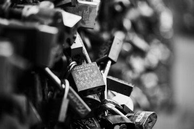 padlocks hanging on fence wire at bridge