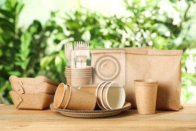 Naklejka Paper dishware on wooden table against blurred background, space for text