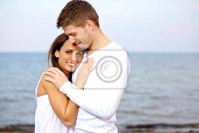 Para Przytulanie na plaży patrząc szczęśliwy