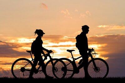 Naklejka para z rowerem na zachód słońca