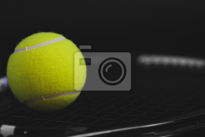 part of new yellow tennis ball on black net racket, copy space on right