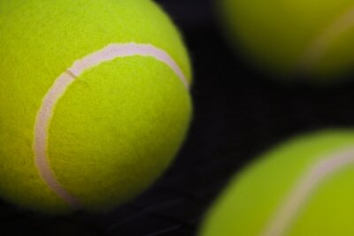 part of new yellow tennis balls on black background