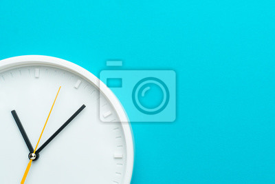 Naklejka Part of white wall clock with yellow second hand hanging on wall. Close up image of plastic wall clock over turquiose blue background with copy space. Photo of time management or time is going concept