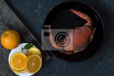 Parze kraba z pomarańczowym kawałkiem na tle drewna.