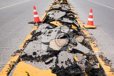 pęknięty asfalt z oznakowaniem linii i bezpiecze? stwa szyszki paskiem pomarańczowo-biały
