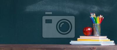 Naklejka Pencil tray and an apple on notebooks on school teacher's desk.