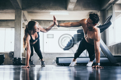 Naklejka Personal trainer helping woman exercising in the sport gym