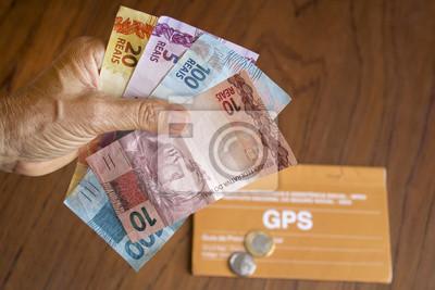 Naklejka Pessoa segurando dinheiro brasileiro para previdência social