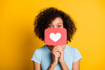 Naklejka Photo of funky playful dark skin curly girl dressed blue t-shirt holding heart like card cover face isolated yellow color background