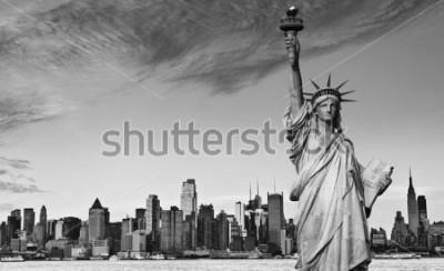 Naklejka photo statue of liberty new york city black and white hi contrast. nyc new york city skyline over Manhattan cityscape midtown. statue of liberty over hudson river in new york city.