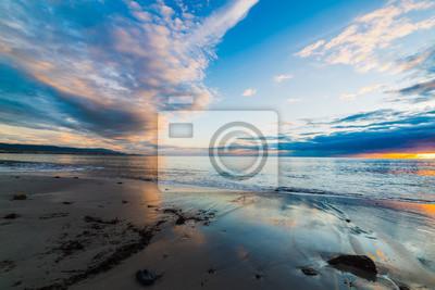 Piasek i skały morzem przy zmierzchem