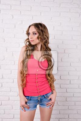 piękna dziewczyna z długimi włosami faliste stojących na białym tle