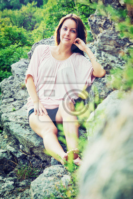 Piękna młoda kobieta siedzi na skale