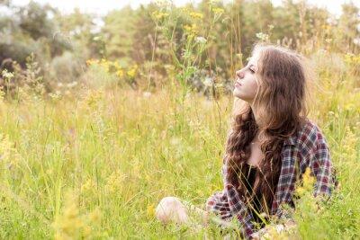Piękna młoda kobieta z długimi kręconymi włosami ubrana w brązowej koszuli wyboru siedzi na łące w wysokiej trawie i delikatny dzikich kwiatów