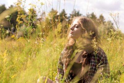 Piękna młoda kobieta z zamkniętymi oczami i długie kręcone brązowe włosy ubrany w koszulę wyboru siedzi na łące w wysokiej trawie i delikatny dzikich kwiatów