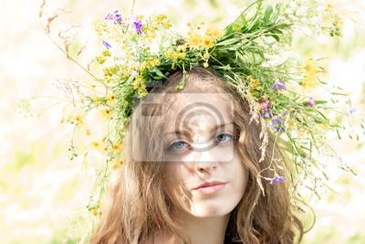 Piękna niebieskooka młoda kobieta z kolorowych wianek wykonany z dzikich kwiatów na głowie.