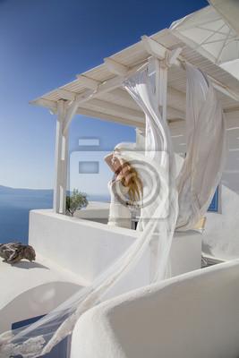 Piękna panna młoda w sukni ślubnej w Santorini z długim welonem
