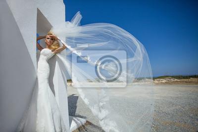 Piekna panna mloda w sukni slubnej w Santorini z długim welonem