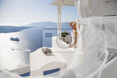 Piękna panna mloda w sukni ślubnej w Santorini z długim welonem