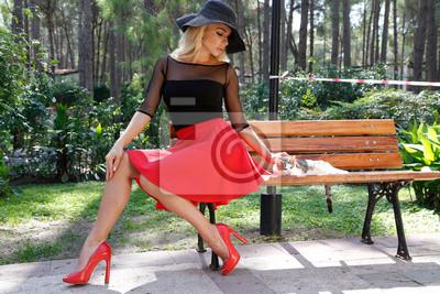 Piękne blond kobieta w czarnym kapeluszu z długimi nogami siedząc