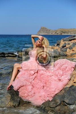 Piękne blond kobieta z długimi nogami w różowej sukni kulowym