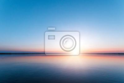Naklejka Piękny, czerwony świt nad jeziorem. Promienie słońca przez mgłę. Błękitne niebo nad jeziorem, nadejdzie poranek, niebo odbija się w wodzie.