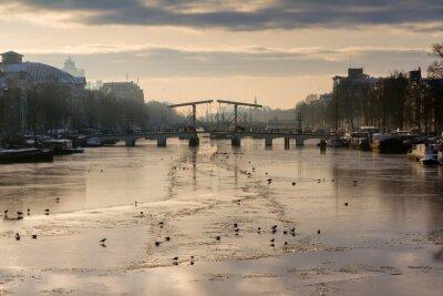 Naklejka Piękny zimowy panorama rzeki Amstel w Amsterdamie, w Holandii, patrząc w kierunku Skinny Bridge.