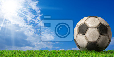 Piłka nożna - Piłka z zielonej trawie / Fragment starego czarno-białe piłki nożnej (piłka nożna) z zielona trawa i błękitne niebo z chmurami i promieni słonecznych