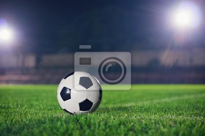 Piłka nożna w nocy. Klasyczna piłka nożna na placu zabaw, odbłyśnik wykonany piękny obiektyw pochodni w tle