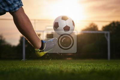 Piłkarz kopa piłkę do celu, zachód słońca w tle