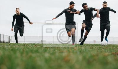 Naklejka Piłkarze grający w piłkę nożną na boisku