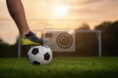 Piłki nożnej piłka z graczem w zmierzchu, piłka nożna brama w tle