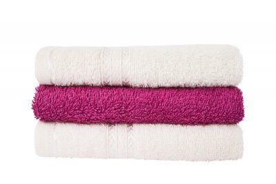 Pink and white bath towels in stack isolated over white background with clipping path
