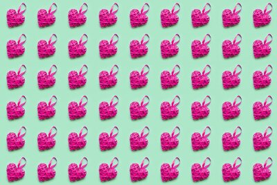 Pink wicker heart on green background. Seamless pattern. Valentines day concept, top view