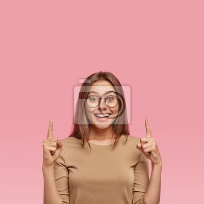 Naklejka Pionowe ujęcie szczęśliwej ciemnowłosej kobiety z zębatym uśmiechem, nosi okrągłe okulary, omawia kuszącą przestrzeń lub miejsce, w którym ubrana jest w beżowy sweter, wskazuje na puste miejsce w górę