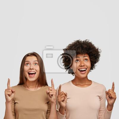 Naklejka Pionowo strzał dwa zadziwiającego mieszanego biegowego kobieta punktu z palcami wskazującymi upwards, szczęśliwych wyrażenia, odizolowywających na białym tle. Tak, jesteśmy numerem jeden. Beztroskie p