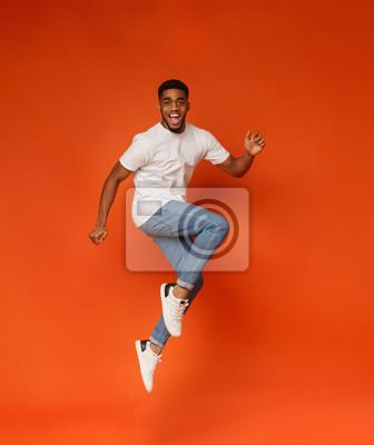 Naklejka Podekscytowany afroamerykański mężczyzna skoki na pomarańczowym tle