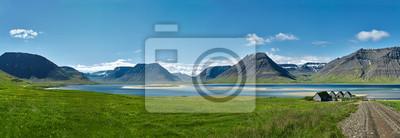 Naklejka Podróż do Islandii. piękny wschód słońca nad oceanem i fiord na Islandii. Islandzki krajobraz z górami, błękitne niebo i zielona trawa na pierwszym planie. Widok drogi do domów na północnym zachodzie