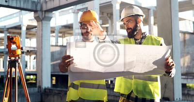 Naklejka Portrait of construction engineers working on building site