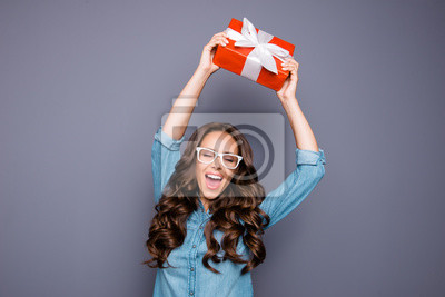 Portrait of her she nice lovely sweet winsome attractive cheerful cheery optimistic wavy-haired lady holding raising up red bow ribbon box isolated over gray pastel background