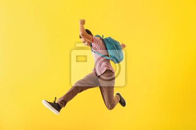Naklejka Portrait of jumping African-American teenage boy on color background