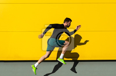 Naklejka Portrait of male athlete running isolated on yellow wall.