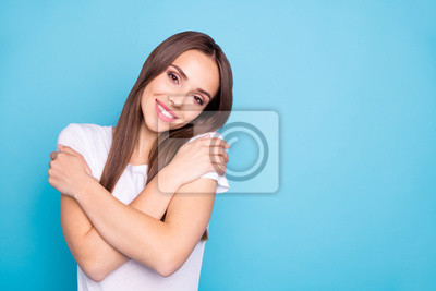 Portrait of nice youth touching her shoulders looking at camera wearing white t-shirt isolated over blue background