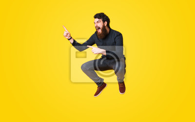 Naklejka Portret krzyczy brodaty mężczyzna i skacze nad żółtym tłem i wskazuje daleko od